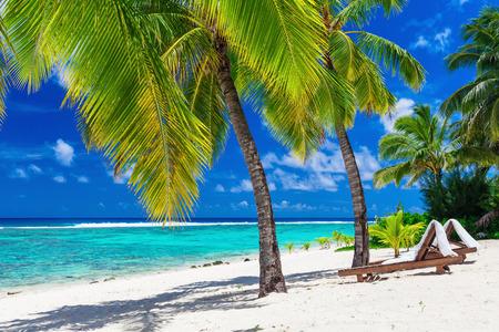 getaways: Camas de playa bajo palmeras de coco con una vista al mar Rarotonga Islas Cook Foto de archivo