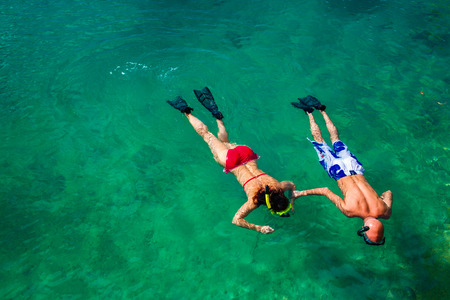 snorkeling: Young couple snorkeling in clean green water over coral reef Stock Photo