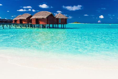 blue lagoon: bungalow sopraelevato e la spiaggia bianca in laguna blu delle Maldive tropicale