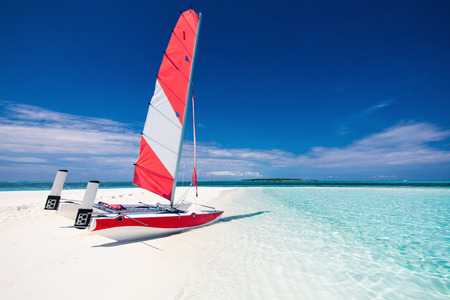 sailboat: Sailing boat with red sail on a beach of deserted tropical island with shallow blue water