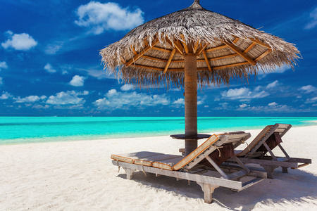 relaxing beach: Two chairs and umbrella on a tropical beach with amazing lagoon view
