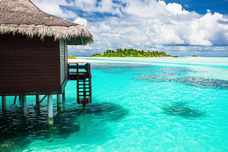 Over water bungalow with steps into amazing blue lagoon with island in distance