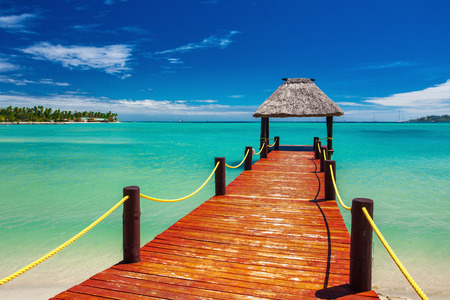 docks: Short red wooden jetty extending to tropical ocean on Fiji Island Stock Photo
