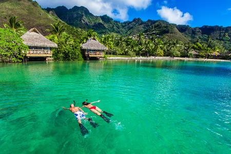 luna de miel: Pareja joven que bucea sobre el filón próxima al centro turístico en una isla tropical con villas sobre el agua