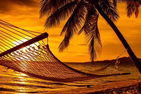 Silhouet van hangmat en palmbomen op een tropisch strand bij zonsondergang