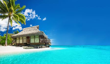 Tropische bungallow op het prachtige strand met een palmboom Redactioneel