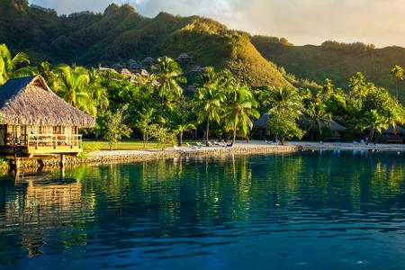 ヤシの木と熱帯のリゾート地での別荘は、日没時に海に反映されます。 写真素材 - 57139928