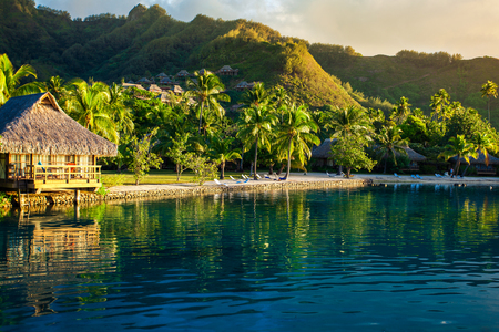 Villas in a tropical resort and with palm trees reflected in the ocean during sunset