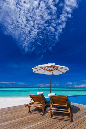 Sun umbrellas and wooden beds on tropical beach with the best view over the pool Stock Photo