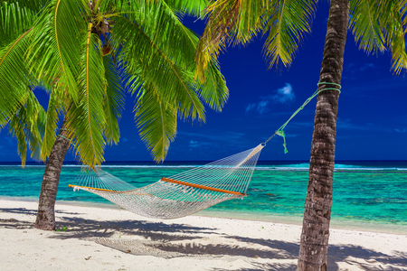 Hammock between palm trees on tropical beach of Rarotonga, Cook Islands, South Pacific Stock Photo