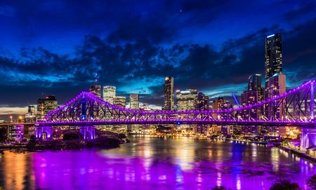 Vibrant night time panorama of Brisbane city with purple lights on Story Bridge, Australia