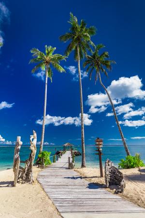 Tropische strandscène met kokosnotenpalmen en pier, Zuid-Pacifische eilanden, Samoa