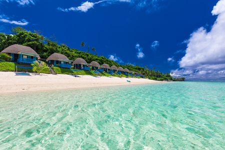 Tropical beach with with coconut palm trees and villas, Polynesia Stock Photo
