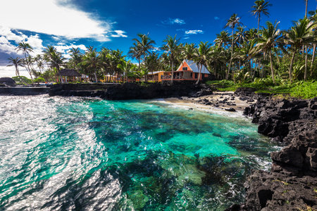 Coral reef and small beach with palm trees on south side of Upolu, Samoa Islands.