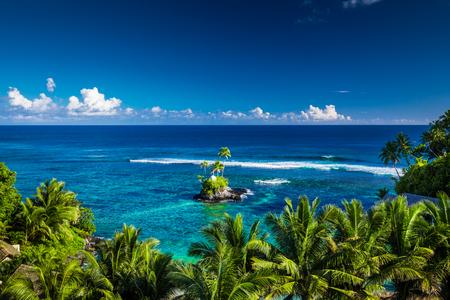 Tropical beach on Samoa Island with palm trees on a small island, Upolu Stock Photo