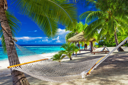 Hammock between palm trees on a vibrant tropical beach of Rarotonga, Cook Islands, South Pacific Stock Photo