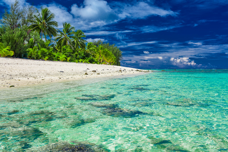 Amazing beach with white sand and black rocks on Rarotonga, Cook Islands Stock Photo