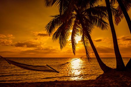 Silueta de hamacas y palmeras en una playa tropical al atardecer, Islas Fiji