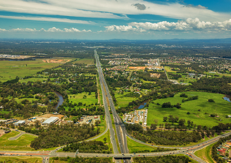Aerial view of Caboolture and Bruce highway to Brisbane with Bribie Island Road crossing, Queensland, Australia