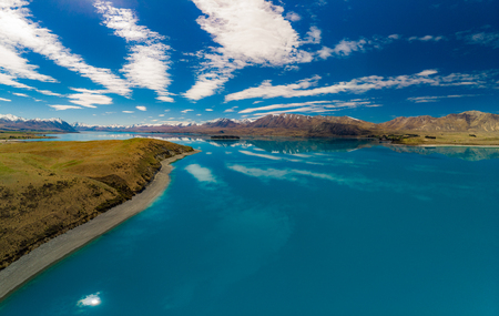 Aerial drone shots of beautiful Lake Tekapo with reflection of sky and mountains, New Zealand