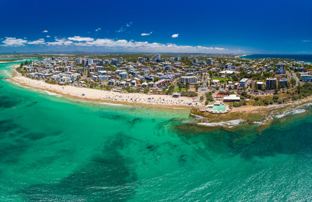 Aerial drone panoramic image of ocean waves on a busy Kings beach, Caloundra, Queensland, Australia