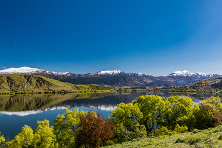 Lake Hayes reflecting Coronet  mountains with snow, near Queenstown, New Zealand 写真素材