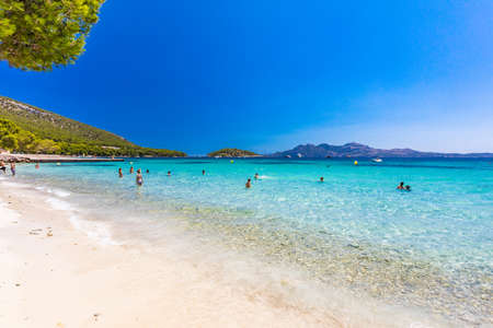 Platja de Formentor, Mallorca, Spain - July 20, 2020: People enjoying the popular beach in summer, Mallorca, Spain.