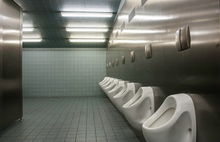 Row of urinal in a public restroom Stock Photo
