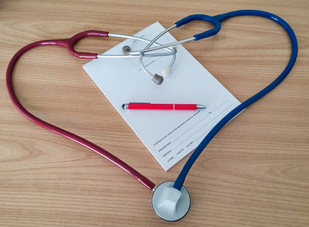 recipe background: Two stethoscopes forming a heart. red right, left blue,red pen and recipe Background wood Stock Photo