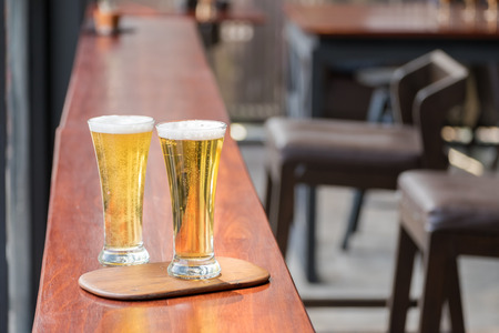 Glass of Beer on wooden table in restaurant Stock Photo