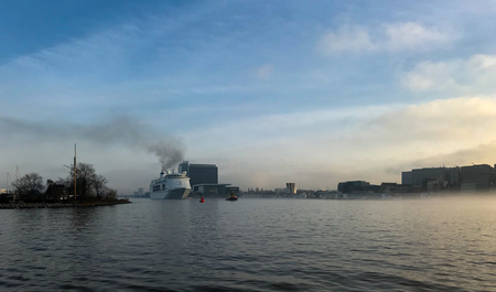 Boat in the mist in Amsterdam harbor in the Netherlands Stock Photo