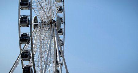 Ferris wheel on a blue sky background in the summer. Low angle vertical shoot