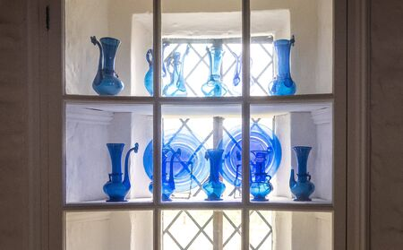 white shelves with glass tableware in a cabinet in front of a window in Sissinghurst Caslte Gardens in Cranwood, England