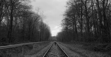 boy runs on a train tracks through the forest in the netherlands