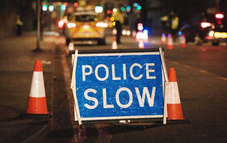 police slow sign on street at night lights bokeh london united kingdom in winter Stock Photo