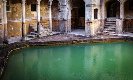 water and buildings in an old roman bath in the city of Bath in the united kingdom england Foto de archivo
