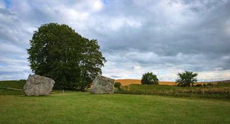 Impressive standing stones from the historic circle in Avebury Wiltshire. Sheep can be seen grazing amongst the massive rocks. united kingdom
