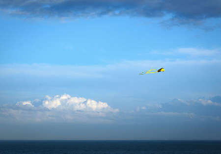 yellow kite against a blue sky with a few clouds above the sea dover uk
