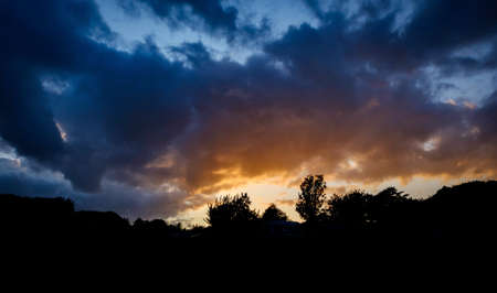 dramatic sunset against mountains with trees and clouds in dover uk Standard-Bild