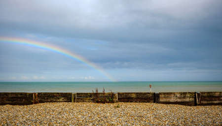 rainbow over the sea behind a pebble beach in dover uk