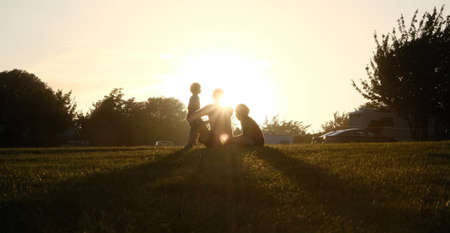 silhouettes of people sitting in the setting sun in dover uk Standard-Bild