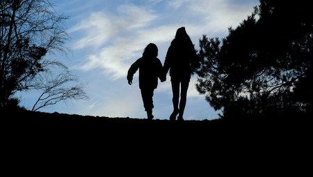 silhouettes of boy and girl walking background. 版權商用圖片