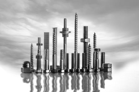 Een skyline gemaakt van lange schroeven, bouten, moeren op een witte achtergrond met wilde wolken Stockfoto