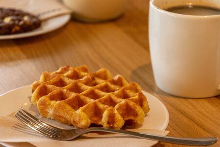 Belgian waffles, cup of coffee on wooden background. Tasty breakfast Stock Photo