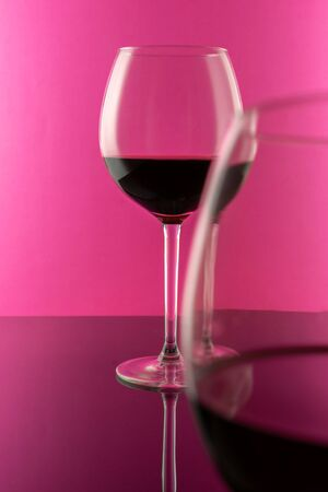 Studio shot of a glass of red wine isolated on pink background closeup. Clean and minimal. Red wine in a big glass. Wine concept. Stockfoto