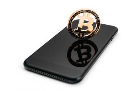 Bitcoin Cash. Gold Cryptocurrency with black smartphone. Falling coins isolated on white. Litecoin, Ethereum Cryptocurrency background. Bitcoin concept Stock Photo