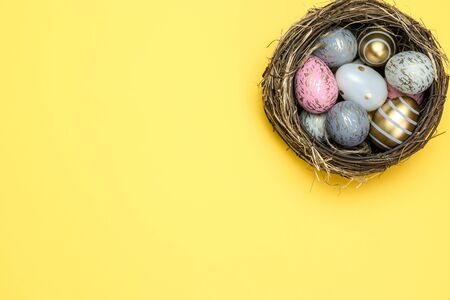 Happy Easter golden shine decorated eggs in basket isolated on yellow background. For greeting card, promotion, poster, flyer, web-banner, article.