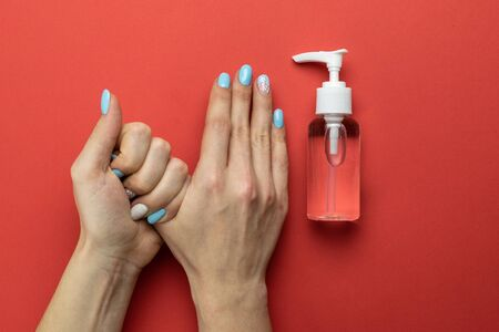 Washing hands isolated on red. Using medical sanitizer gel in lab gloves on red background. Clear sanitizer in pump bottle. Cleansing hand hygiene for coronavirus outbreak prevention 版權商用圖片