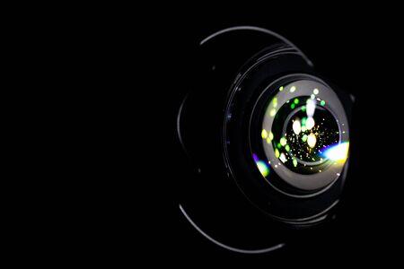 Lense flare lights on shutter. Reflection on photo, video camera on black background. Sunlight abstract bokeh in digital macro studio shot