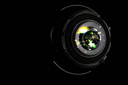 Lense flare lights on shutter. Reflection on photo, video camera on black background. Sunlight abstract bokeh in digital macro studio shot. Stock Photo
